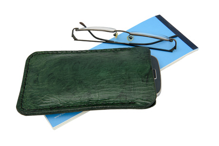 Handmade, green leather mobile case and spectacles with a blue cheque book Stock Photo