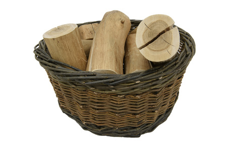 Handmade, dark brown, woven willow basket containing logs.