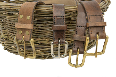 buckles: Handmade leather belts with metal buckles  arranged over a hand woven willow basket
