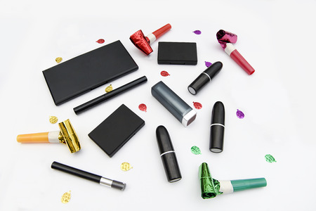 Assorted makeup items arranged with party decorations on a white background