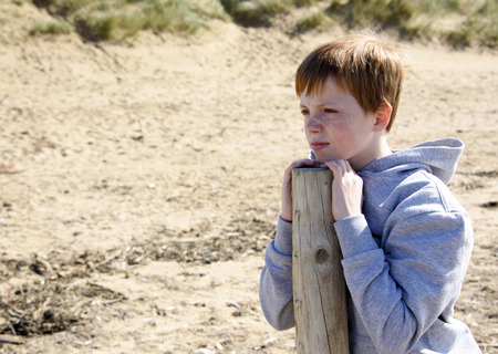 Young boy, leaning on a post and gazing into the distance on the beach at St Annes on Sea, Lancashire, UK