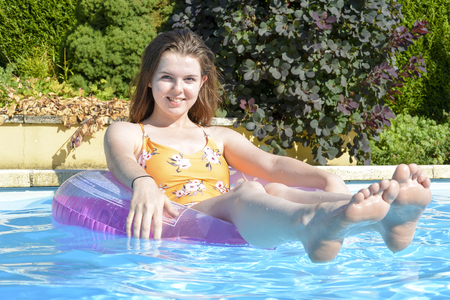 Smiling, teenage girl floating in an inflatable ring in an outdoor swimming pool