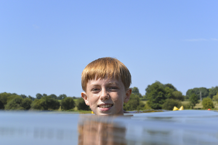 Young, auburn haired boy treading water in a lake