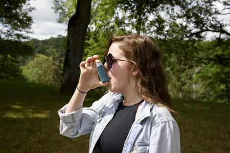 Long haired, teenage girl in denim jacket using a blue asthma inhaler. Taken in woodland on a sunny day.