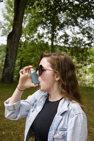 Teenage girl using inhaler (portrait). Long haired, teenage girl in denim jacket using a blue asthma inhaler. Taken in woodland on a sunny day. Stock Photo