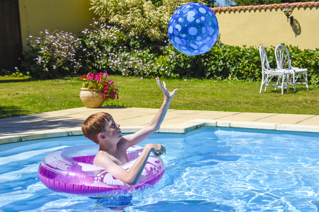A teenage boy in a pink,  inflatable ring, catching a ball in a swimming pool