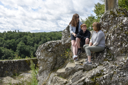 A mother a teenage daughter and teenage son chatting in the outdoors. Taken in Rochechaurt, Limousin, France