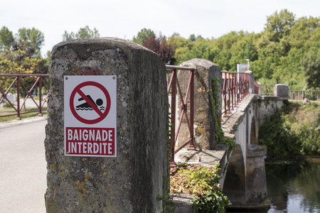 No Swimming sign in French, on a bridge over a tributary of the Charente in Jarnac, France.