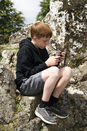 Teenage boy using his smart phone whilst outside.