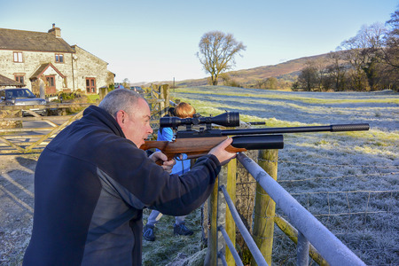 Man and teenage boy firing an air rifle on farmland on a cold, frosty day. Stock Photo