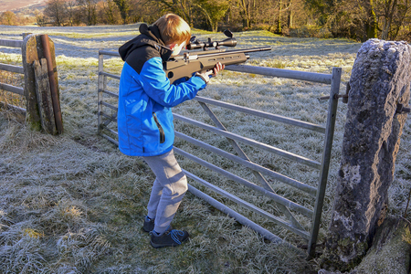 Teenage boy firing an air rifle on farmland on a cold, frosty day Stock Photo