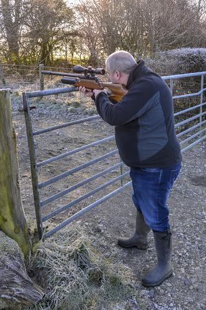Middle-aged man firing an air rifle on farmland on a cold, frosty day.