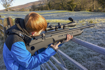 Teenage boy firing an air rifle on farmland on a cold, frosty day.