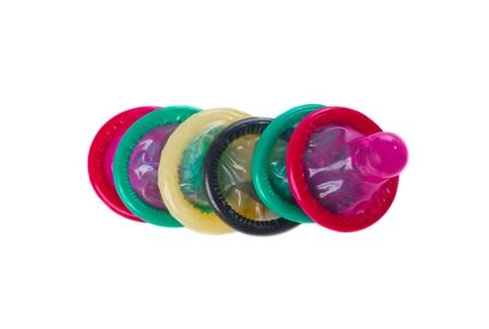Multi gekleurde condomsin een rij die op wit wordt geïsoleerd Stockfoto