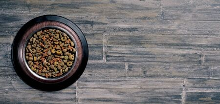 Bowl with dry food for pets on wooden background. Panoramic image with copy space.