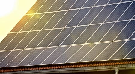 Photovoltaic. Roof with solar panels at sunset. 版權商用圖片