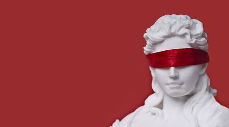 Close-up of lady's justice with red blindfold. Panoramic image with copy space. Standard-Bild - 136788563