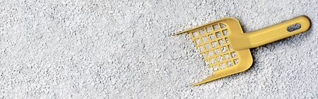 Yellow plastic shovel on cat litter. Panoramic image with copy space.