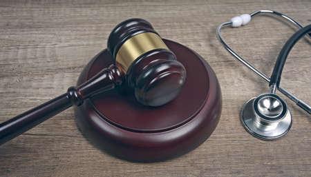 Judge gavel beside medical stethoscope on wooden table. Medical law concept. Stock fotó