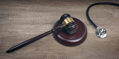 Close-up of Judge gavel beside medical stethoscope on wooden table. Panoramic image.