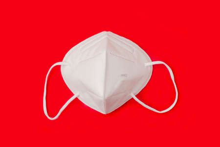 FFP 2 n95 protective face mask on red background. Protection and prevention against  virus Standard-Bild
