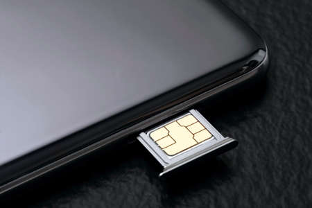 Close up of a cell phone with sim card on black background. Standard-Bild