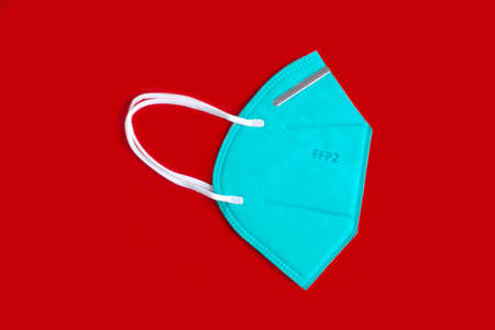 Side view of green FFP2 n95 protective face mask,  virus prevention. Isolated on red background.