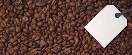 Top view of a bunch of roasted coffee beans. Panoramic image with label for your individual text.
