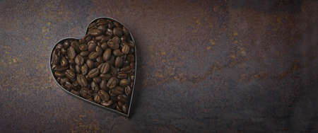 Coffee beans in heart shape on grunge background. Panoramic image with copy space Standard-Bild