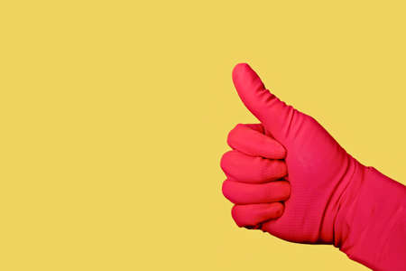 Unrecognizable person with pink glove make Like sign in front of yellow background.