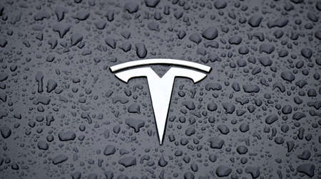 Neu-Ulm, Bavaria, Germany - May 26, 2021: Close up of a Tesla car logo on metallic surface with rain drops. Editorial