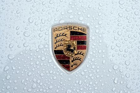 Neu-Ulm, Bavaria, Germany - May 21, 2021: Close up of a Porsche car logo on metallic surface with rain drops. Editorial