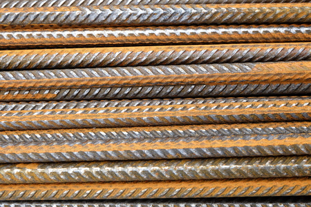 a closeup of rusty horizontally stacked steel division reinforcement bars (rebar)