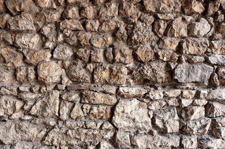 varying: stone wall made of irregular and rough rocks Stock Photo