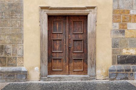 door casing: a wooden double door with rectangle door frame in a stone wall Stock Photo