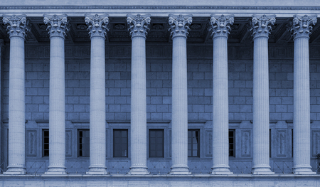 a row of corinthian columns of a public law court in Lyon, France - blue color tone