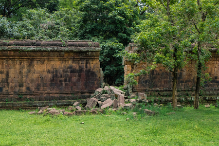jailbreak: a stone wall of an ancient ruin with a big gap from a break through - angkor Stock Photo