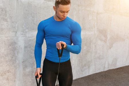 Handsome athletic young man in sportswear outfit posing and doing exercises with elastic expander Banco de Imagens