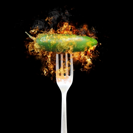 Hot green jalapeno pepper on fire with fork Stock Photo