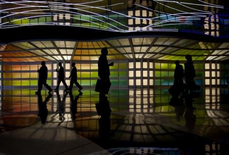 Pedestrian walking through neon tunnel