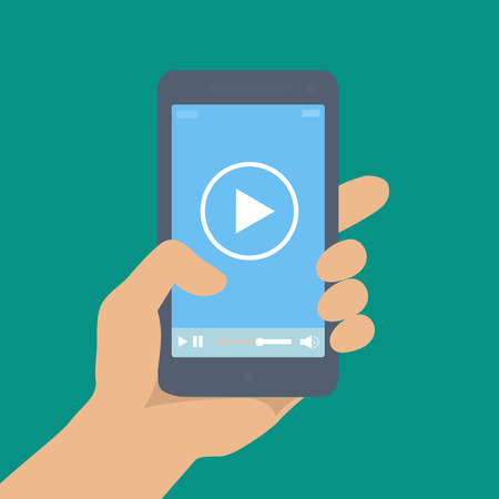 Mobile phone with video player on the screen in the human hand or movie app