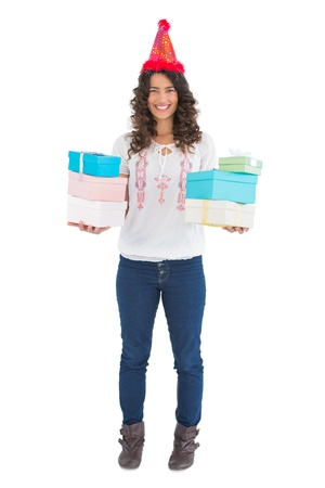 Smiling casual brunette wearing party hat holding presents while posing on white background photo