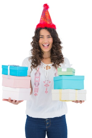 Happy casual brunette wearing party hat holding presents while posing on white background photo