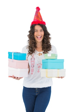 Cheerful casual brunette with party hat holding presents while posing on white background photo