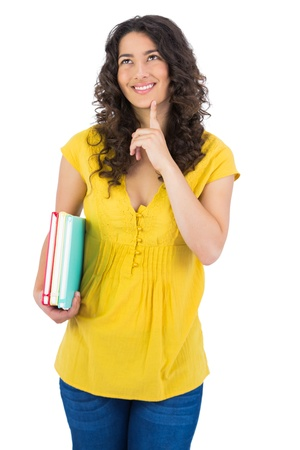 Cheerful curly haired student on white background holding notebooks photo