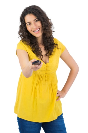 changing channel: Smiling curly haired pretty woman on white background changing channel with remote