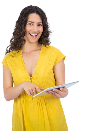 scrolling: Smiling casual young woman on white background scrolling on her tablet computer