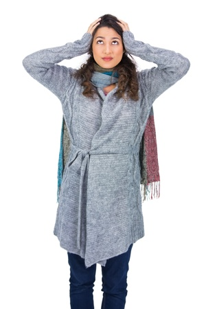 Anxious pretty brunette wearing winter clothes posing on white background photo