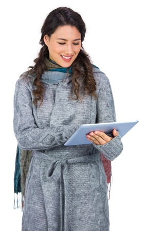 Relaxed brunette wearing winter clothes holding her tablet while posing on white background photo