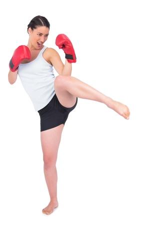 Slender model with boxing gloves kicking while posing on white background photo